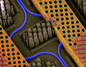Angled view of a portion of an IBM chip showing blue optical waveguides transmitting high-speed optical signals and yellow copper wires carrying high-speed electrical signals. IBM Silicon Nanophotonics technology is capable of integrating optical and electrical circuits side-by-side on the same chip.